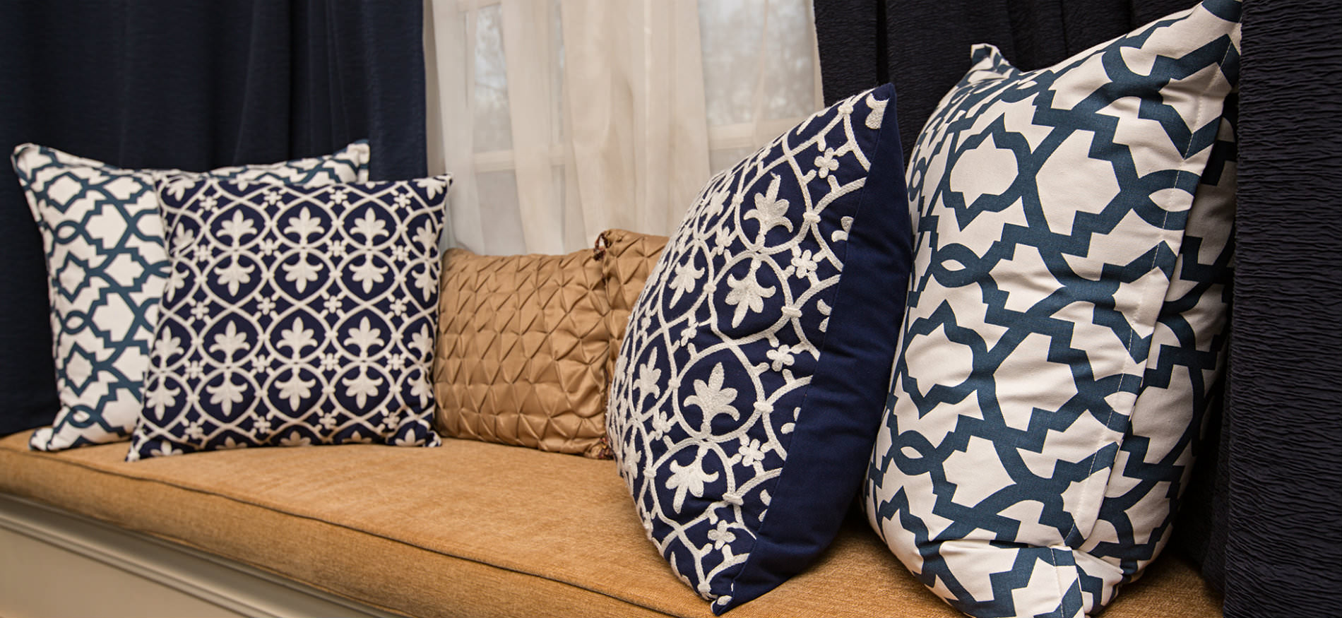 Window seat with a gold cushion and pillow and four pillows in navy and white with white sheers and navy curtains