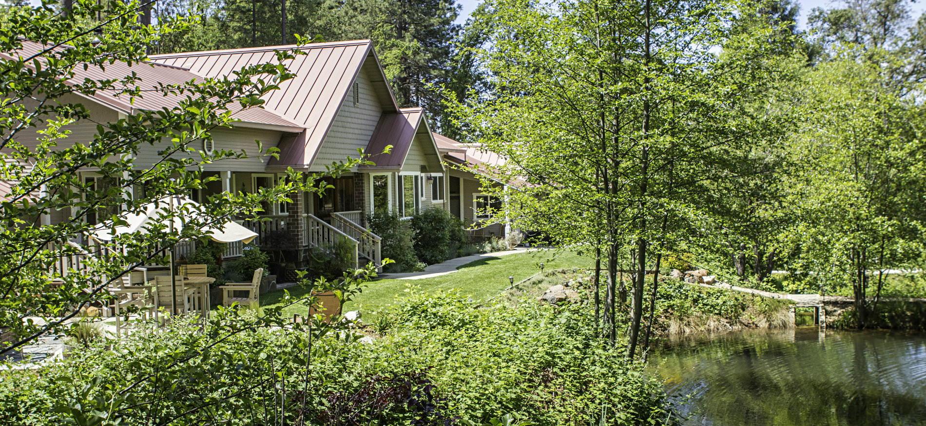 Exterior view of tan cottage with red metal gable roof, lots of lush greenery, a pond and blue skies