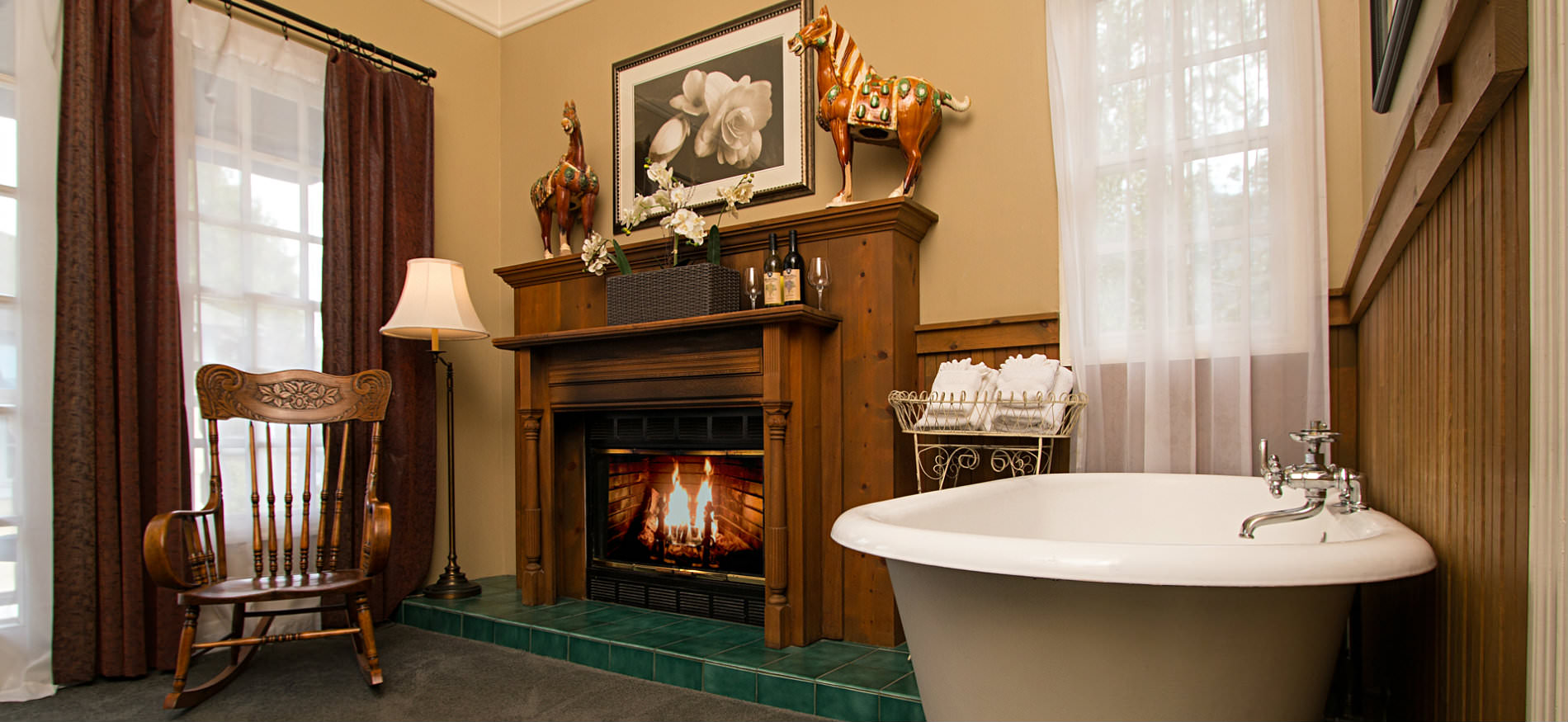 Tan room and fireplace with wood mantle surround, a wood rocking chair, and white freestanding tub