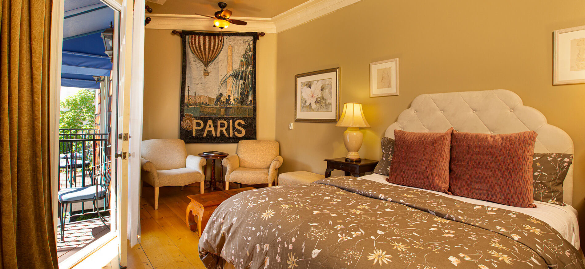 cream and yellow bedroom with tan colored comforter, red pillows, night stand with lamp, pictures on wall and Paris Banner hanging