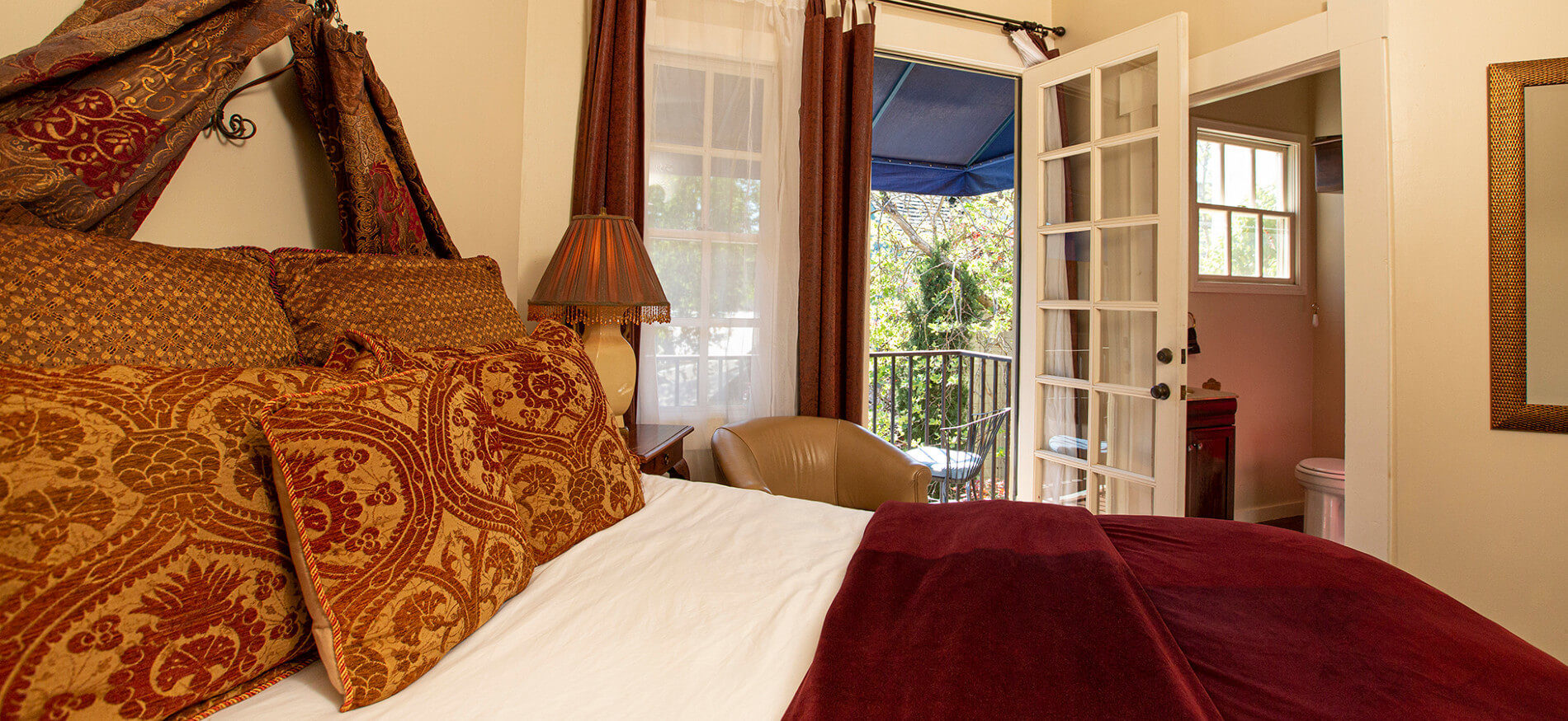 Close up of bed with rich red and gold pillows and wine colored bedspread, bedside lamp, leather chair and French doors