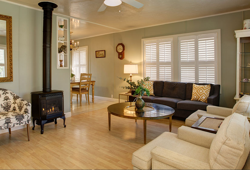 Large living room & dining room with olive walls and wood floors, yellow chairs, brown couch, wood-burning stove.