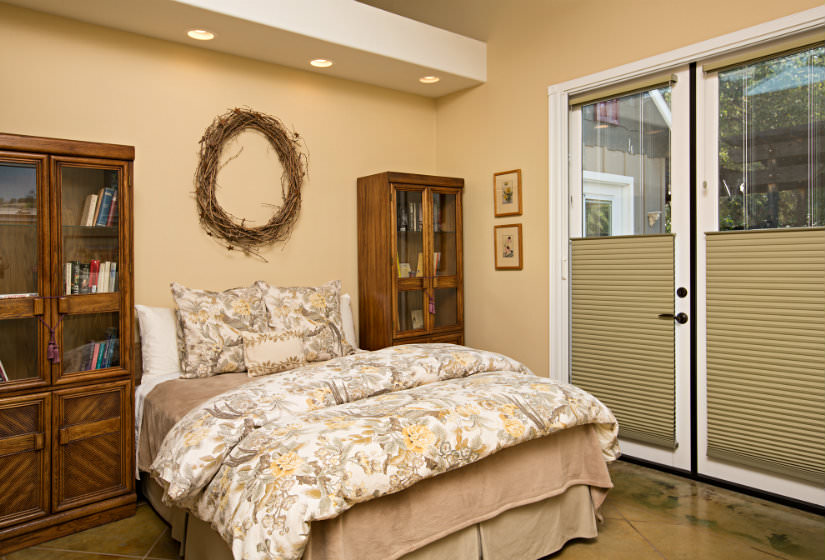Warm tan bedroom with bed with white tan gray and yellow floral comforter flanked by two wood bookcases