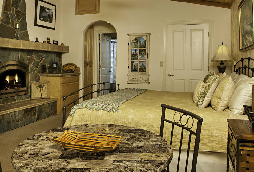 Charming vaulted bedroom with stone fireplace, cream walls, tan carpet and dark metal bed with gold bedspread