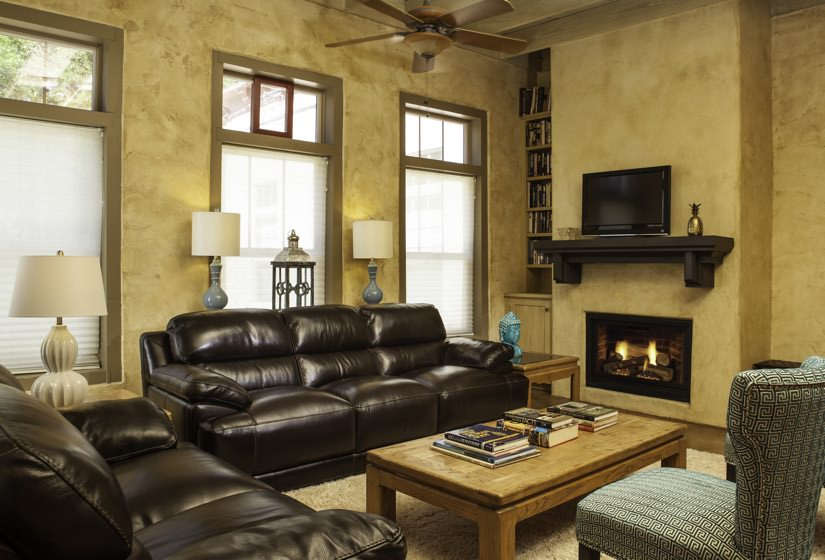 Living room with gold walls, brown leather furniture, a fire in the fireplace and three windows topped with transom windows