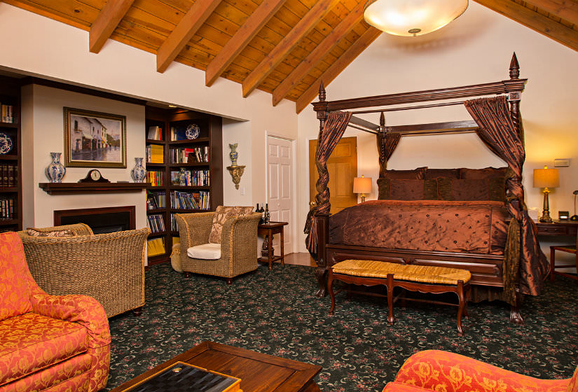Large vaulted suite with four poster bed, bookshelves flanking fireplace with two chairs, and orange chairs with coffee table