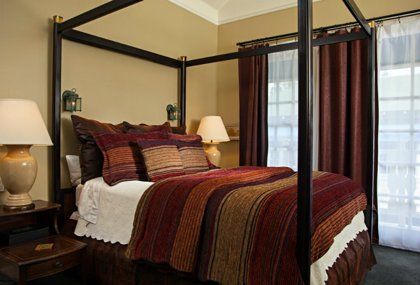 Dark four poster bed with red, brown and gold striped bedspread, large window with red curtains, two nightstands with lamps