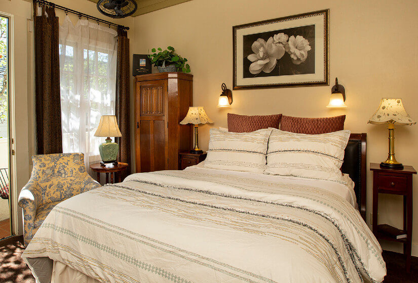 Bed with white comforter and pillows, ivory walls, floral picture and two sconces over bed, three nightstands with lamps