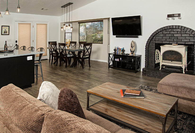 Large room with island seating, black dining table with six chairs, black brick arched fireplace, brown furniture and wood floors