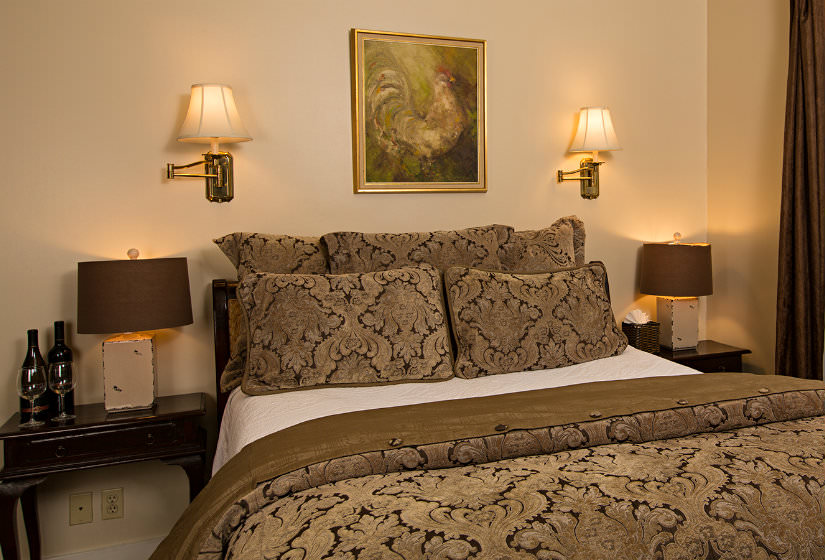 Brown and black pillows and comforter on bed, two nightstands with lamps, two sconces and framed rooster print over bed