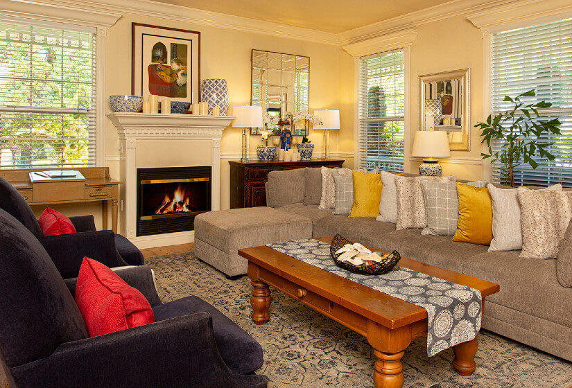 tan couch with ottoman in front of window, coffee table with runner, 2 brown chairs, fireplace, lamps on stands, desk