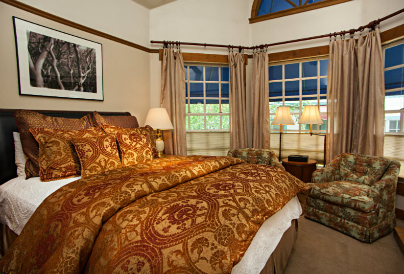 Bedroom with bay window, bed covered in red and gold pillows and comforter, two chairs and small table