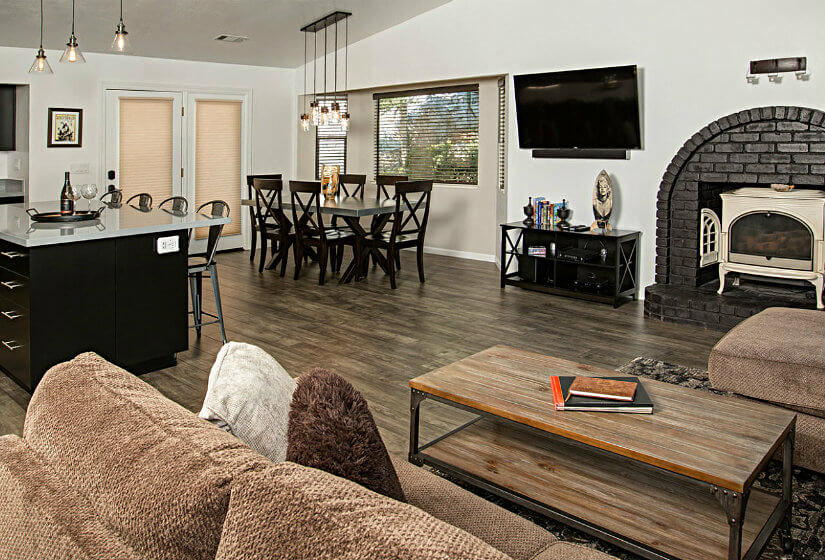 Large room with kitchenette, fireplace, and overstuffed brown furniture